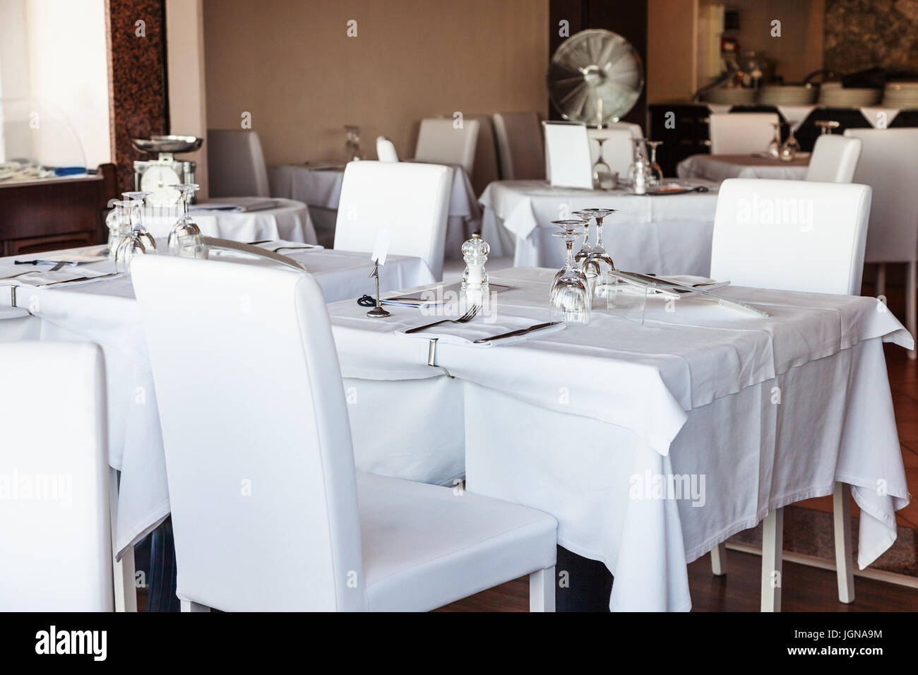 Sedie di pelle bianca e tavoli coperti da tovaglie bianche nel ...