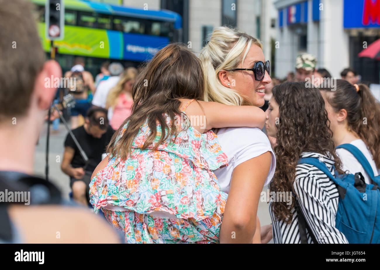 Giovane madre portando la sua giovane figlia sul suo indietro attraverso la folla in una frenetica città affollata. Immagini Stock