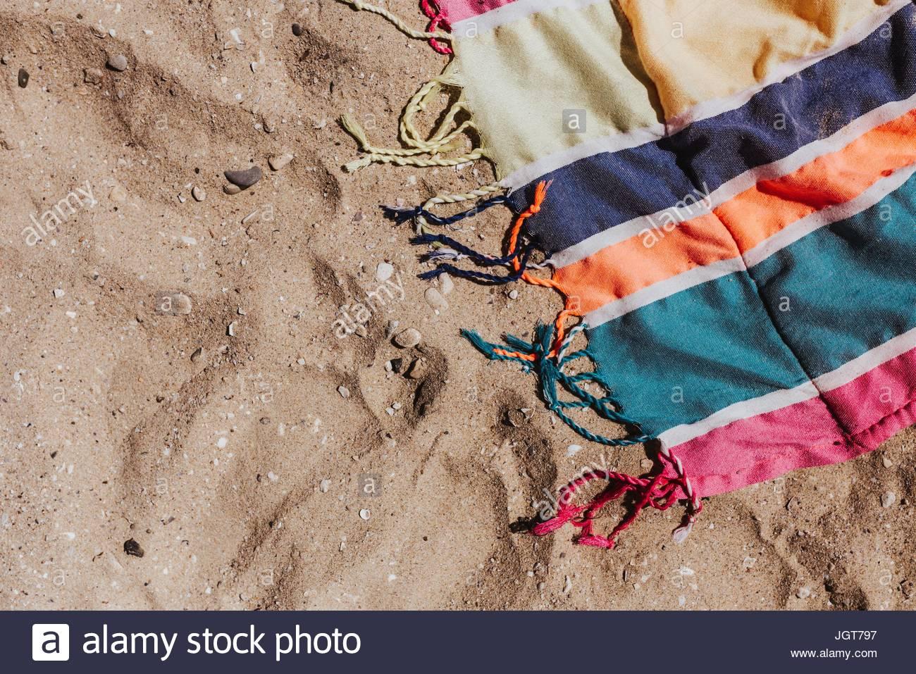 Un colorato telo da spiaggia che è sulla sabbia. Immagini Stock