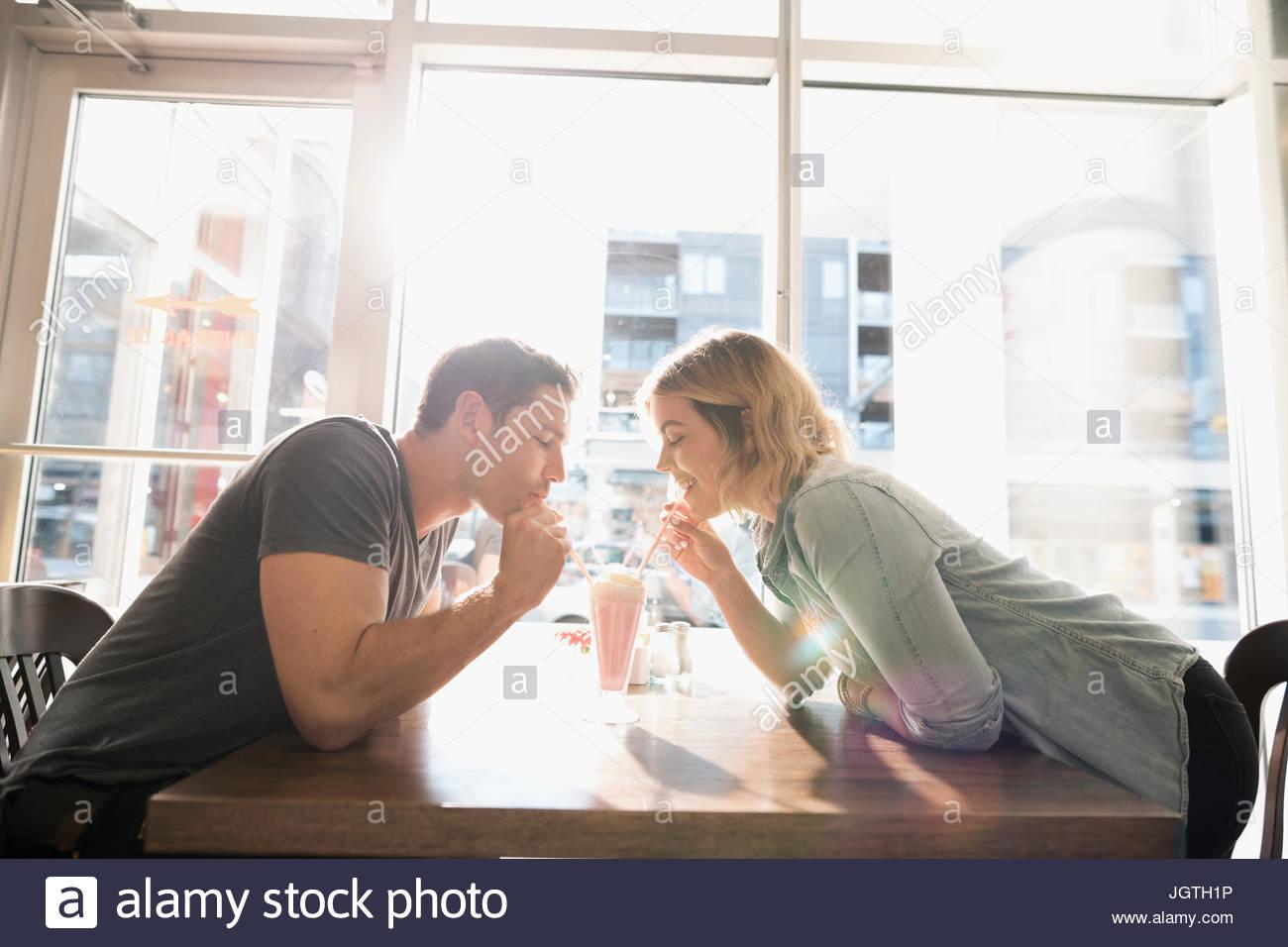 Coppia giovane la condivisione frullato al sunny diner tabella Immagini Stock