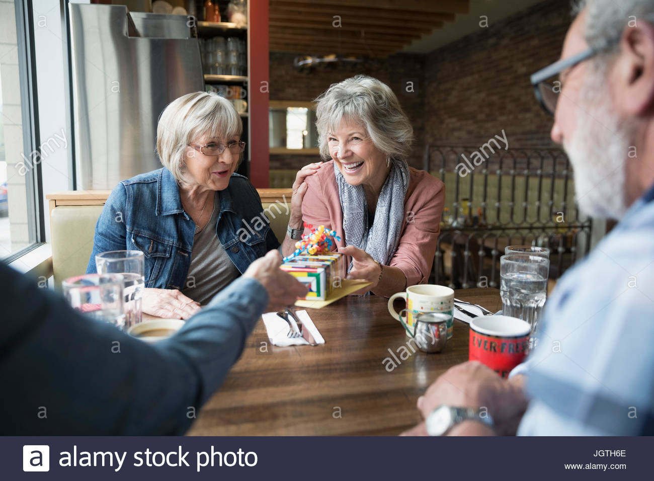 Sorridente donna senior ricevere regalo di compleanno da amico in diner booth Immagini Stock