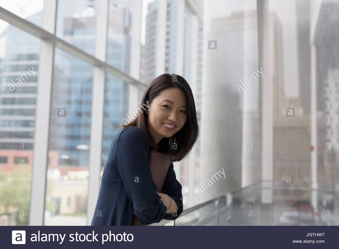 Ritratto imprenditrice sorridente in ufficio highrise corridoio Immagini Stock