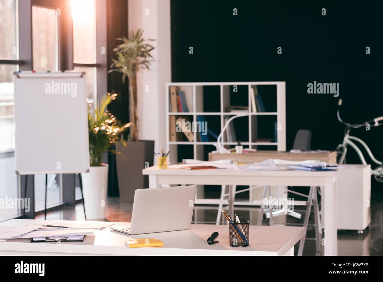 Ambiente di lavoro vuoto con il computer portatile, il blocco note e documenti in ufficio moderno Immagini Stock