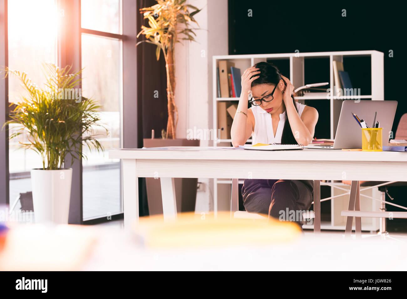Stanco asian imprenditrice seduti al posto di lavoro e il lavoro in ufficio moderno Immagini Stock