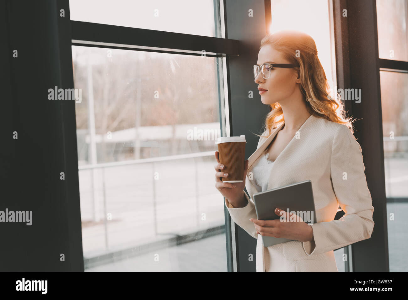 Attraente pensieroso imprenditrice in abito bianco con tavoletta digitale e caffè in piedi alla finestra in Immagini Stock