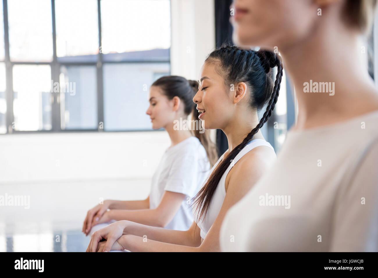 Vista laterale di giovani donne in sportswear meditando a lezione di yoga Immagini Stock