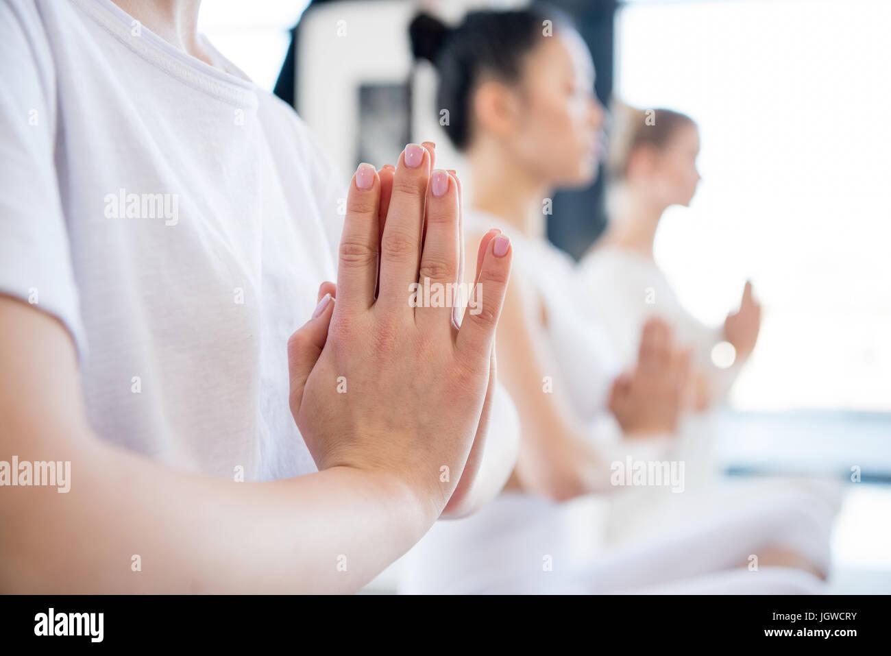 Concentrato di giovani donne meditando in lotus posano con Namaste mudra gesto in ambienti interni Immagini Stock