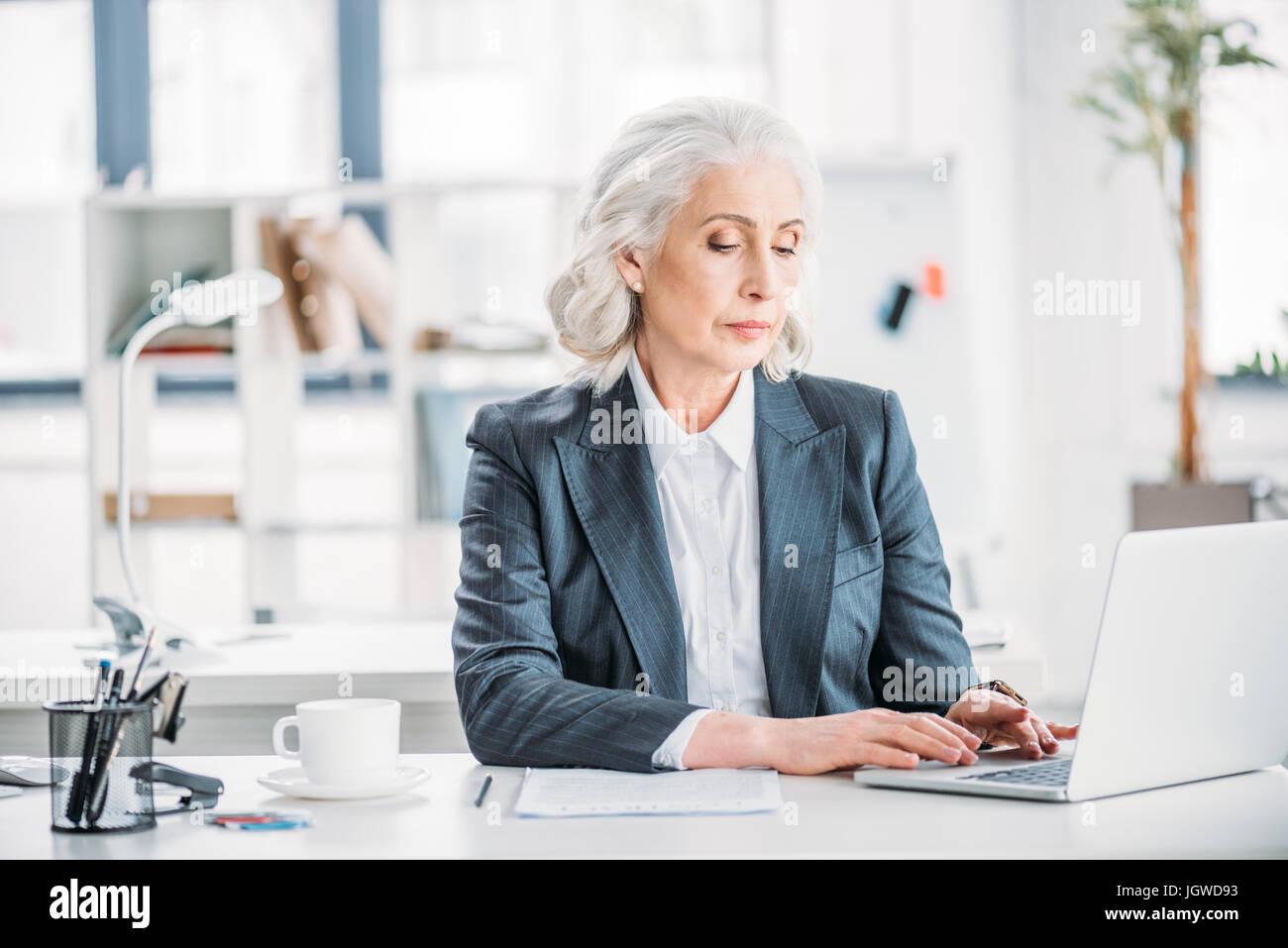 Ritratto di fiducioso imprenditrice digitando su laptop al lavoro in ufficio moderno Immagini Stock