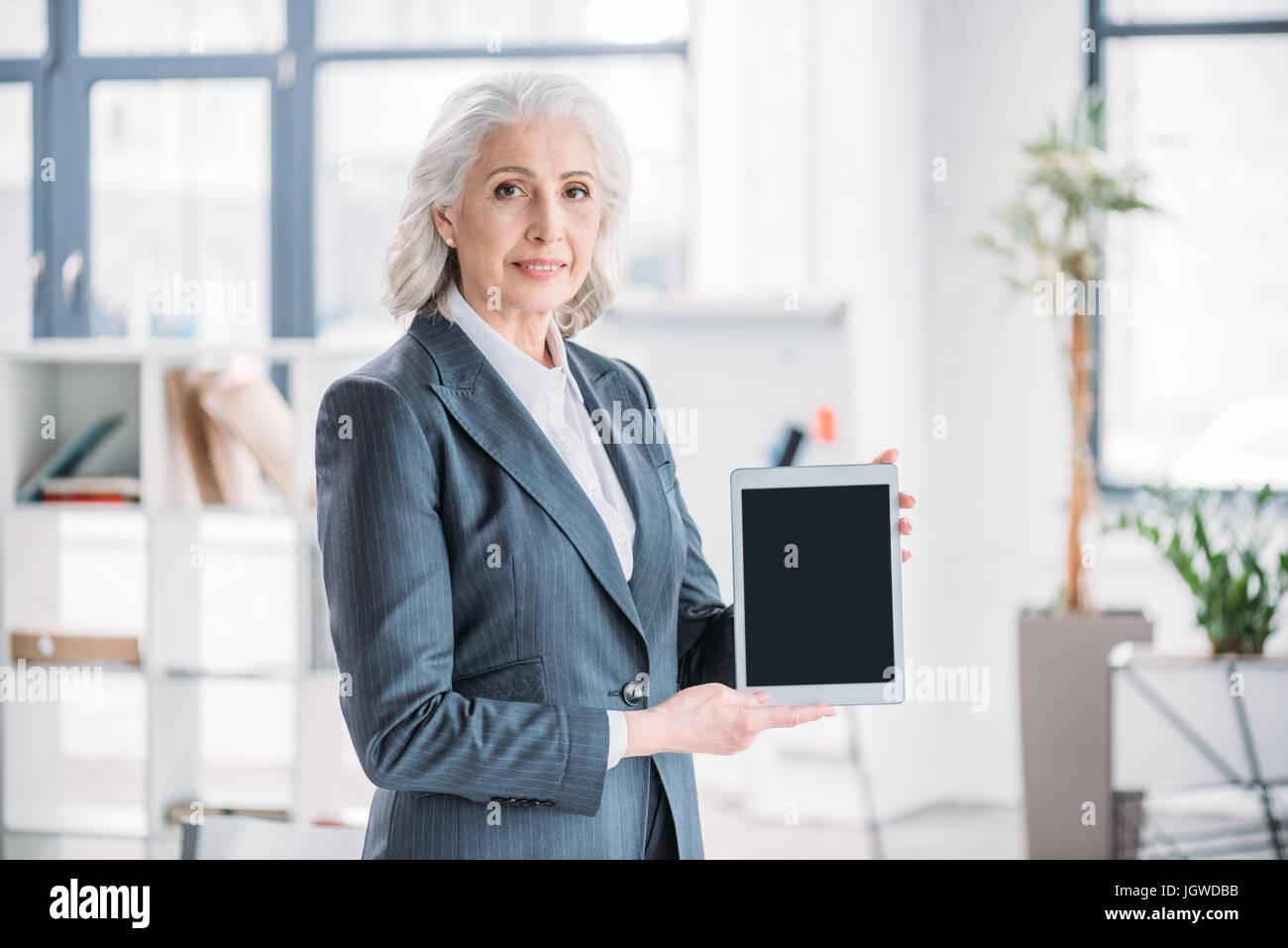 Sorridente imprenditrice senior in piedi in ufficio e azienda tavoletta digitale con schermo vuoto Immagini Stock