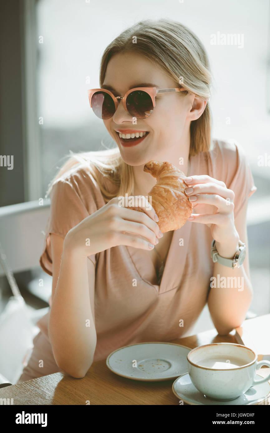 Attraente ragazza caucasica in occhiali da sole con croissant al cafe, aventi il concetto di pranzo Immagini Stock