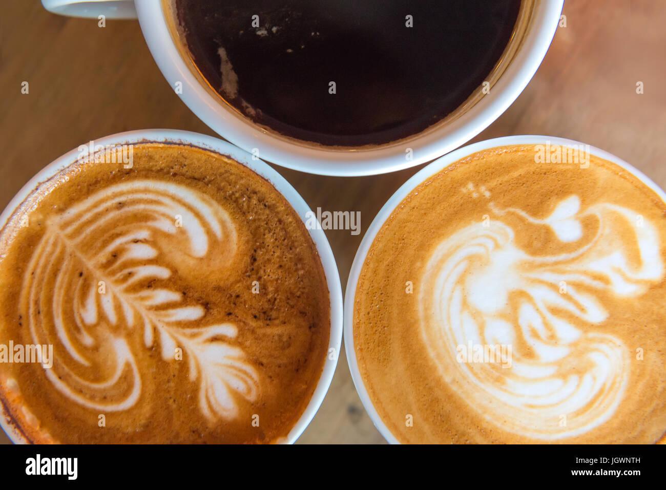 Latte art caffè o cappuccino sul tavolo di legno dello sfondo. Immagini Stock
