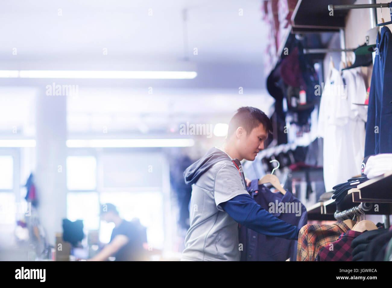 Giovane maschio guidatore di skateboard guardando shirt nel negozio di skateboard Immagini Stock
