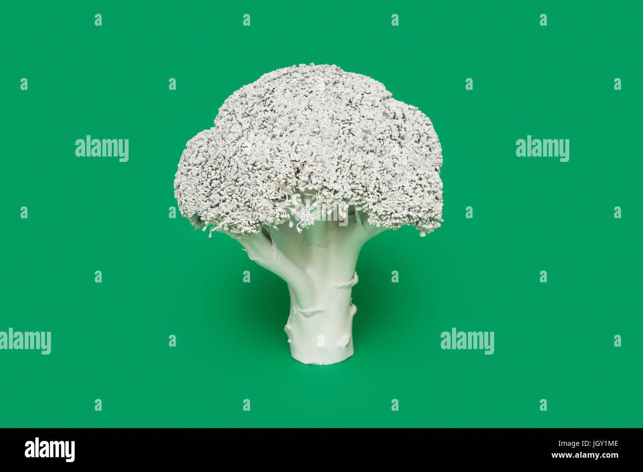 Broccoli dipinto di bianco su sfondo verde Immagini Stock