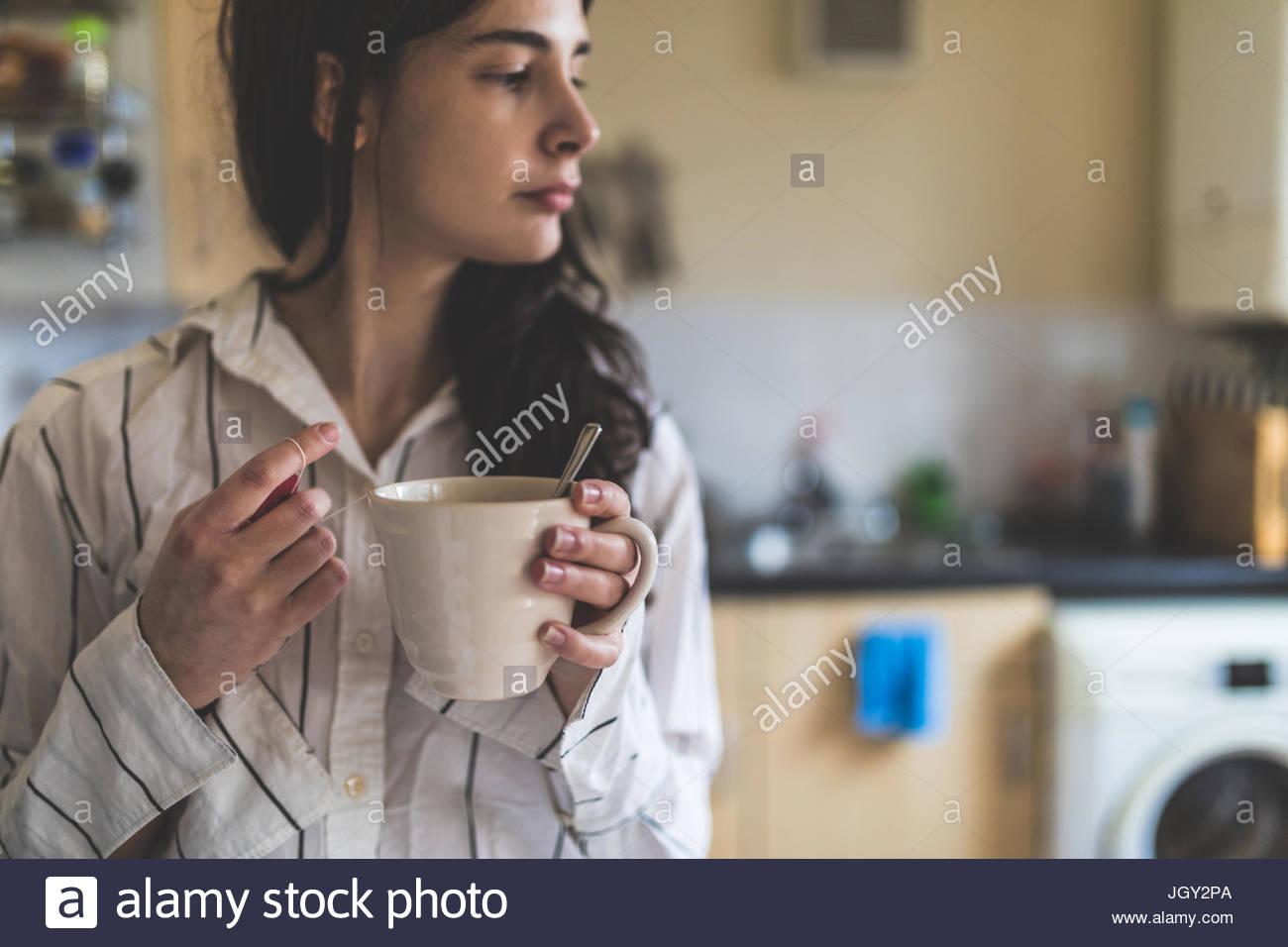 Giovane donna di casa, indossando pigiami, tenendo tazza da caffè Immagini Stock