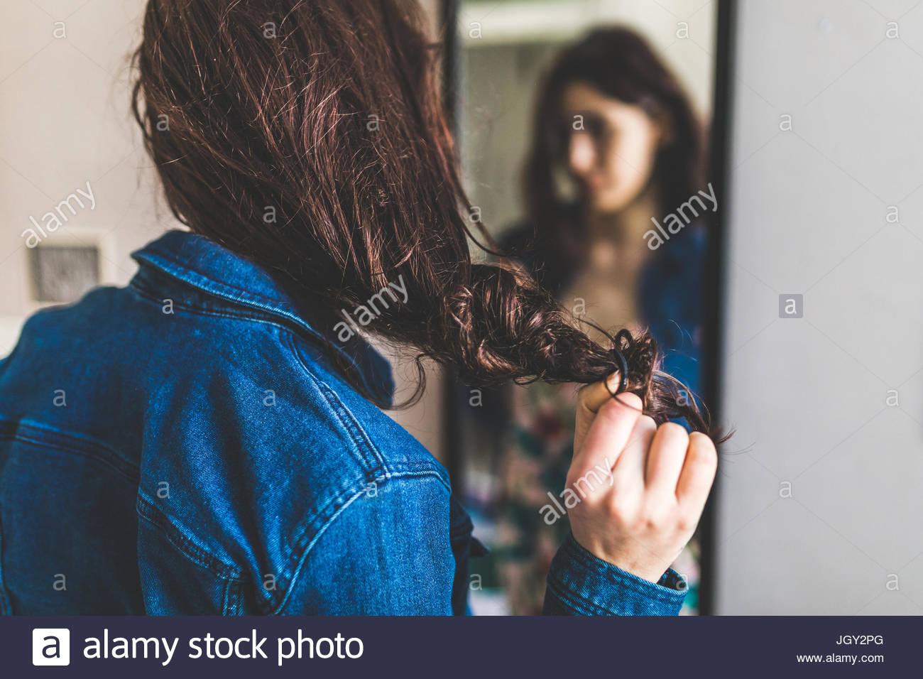 Giovane donna in piedi di fronte a specchio, tira i capelli-band da capelli, vista posteriore Immagini Stock