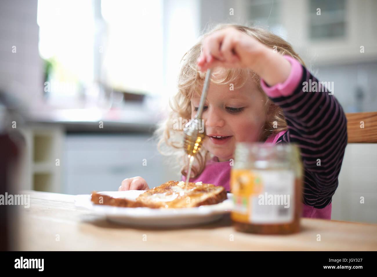 Giovane ragazza seduta al tavolo della cucina, drizzling miele su pane tostato Foto Stock