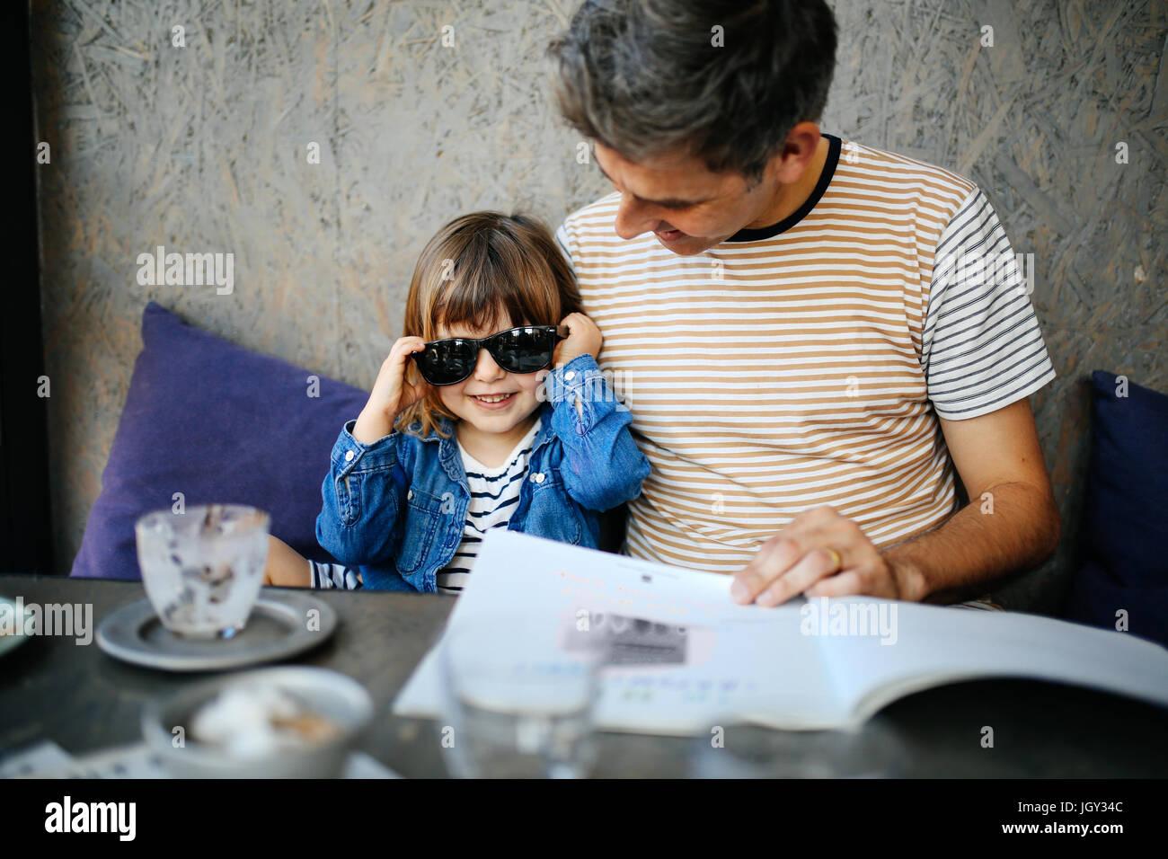 Ragazza che gioca con il padre di occhiali da sole in cafe Immagini Stock