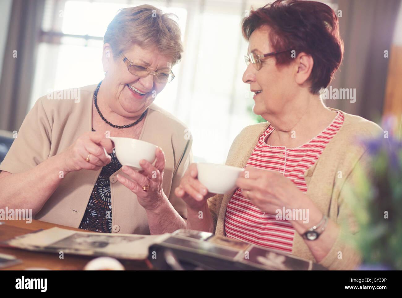 Due senior donne ridere guardando un album di foto sul tavolo Immagini Stock
