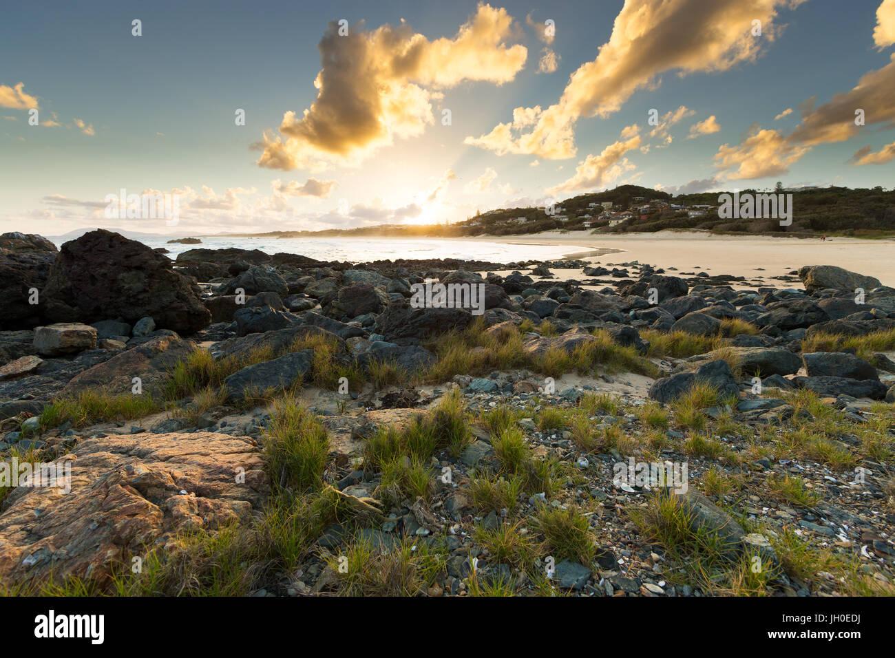 Il sole tramonta su una vivace scena di spiaggia in Port Macquarie, Australia, illuminando le nubi circostanti, Immagini Stock