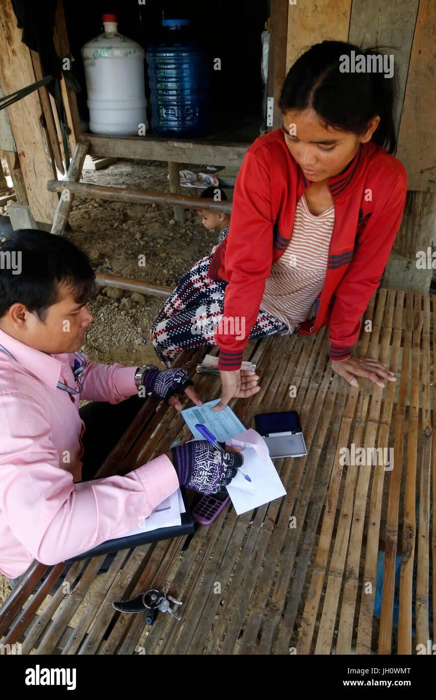 La microfinanza credit officer e client nella propria casa. Cambogia. Immagini Stock