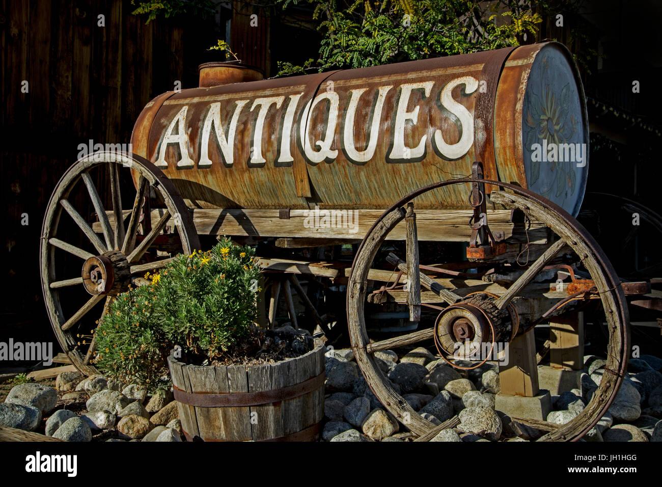 Un segno per un negozio di antiquariato dipinta sulla fiancata di un ripartiti a cavallo il cisterna d'acqua. Immagini Stock