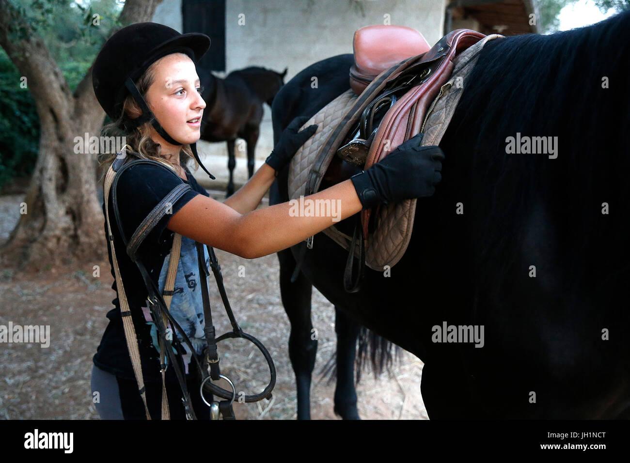 Adolescente unsaddling un cavallo. L'Italia. Immagini Stock