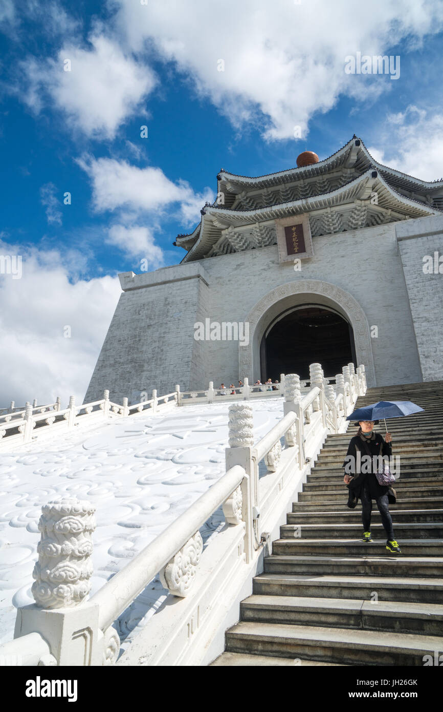 Donna con sun-ombrello di schermatura scendendo gli scalini che portano fino a Chiang Kai-Shek Memorial Hall di Immagini Stock