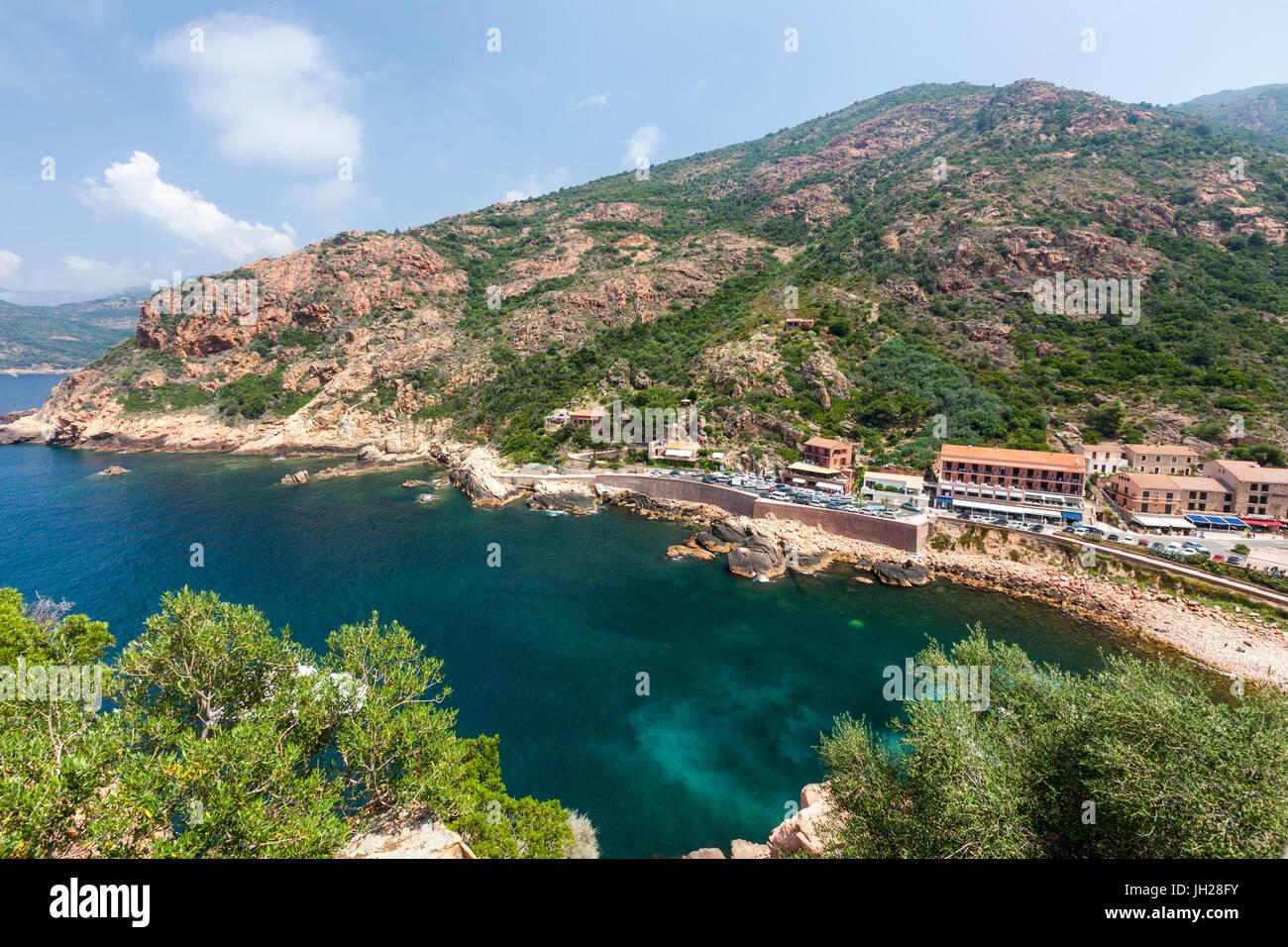 Vista superiore del mare turchese incorniciato dal verde della vegetazione e il tipico villaggio di Porto, Sud Corsica, Immagini Stock