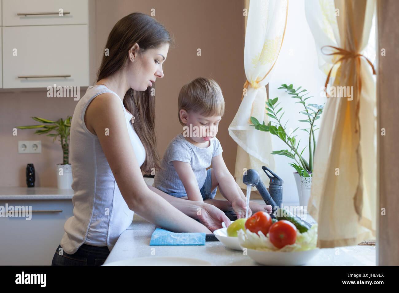 Cucina mamma figlio lavare frutta e verdura Immagini Stock