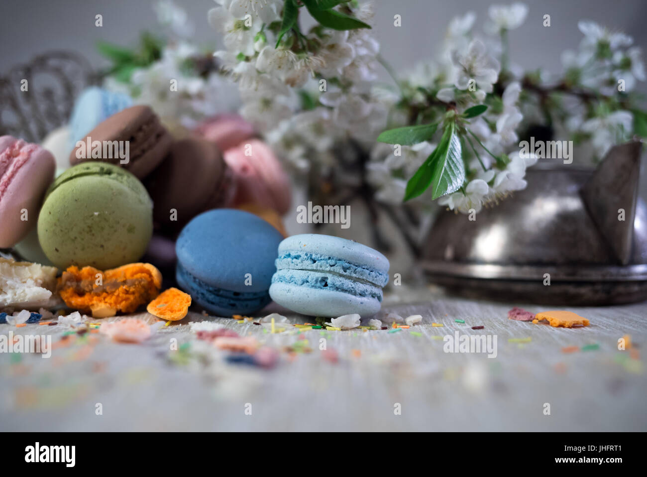 Amaretti multicolore su una tabella con vaso orientale e il ramo di ciliegio in fiore Immagini Stock