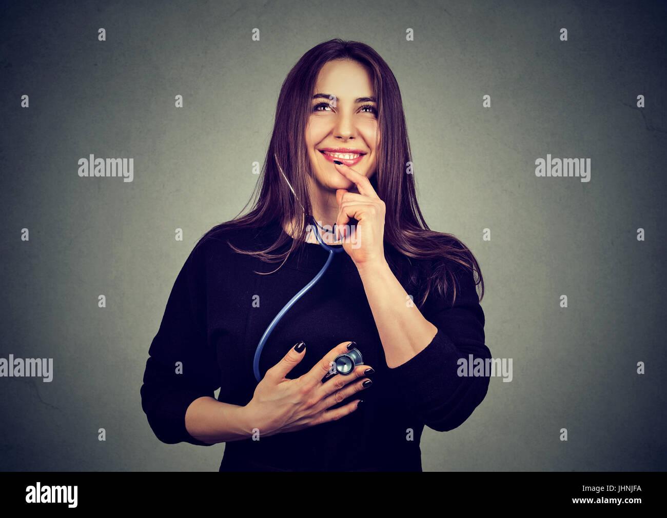Donna ascoltando il suo cuore con uno stetoscopio Foto Stock