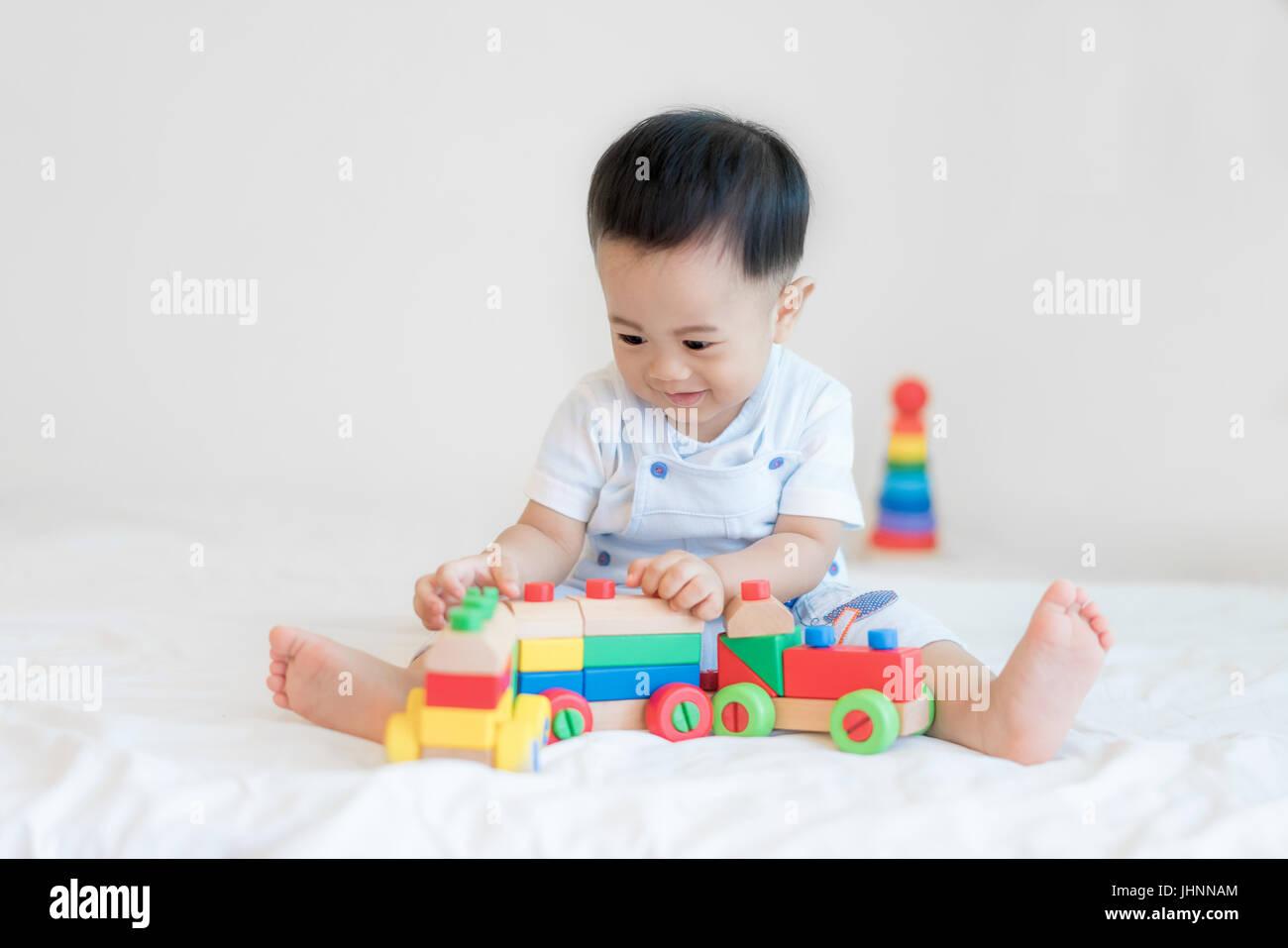 a3f2e890d2 Adorabili Asian baby boy 9 mesi seduta sul letto e a giocare con i colori  del treno in legno giocattoli a casa.