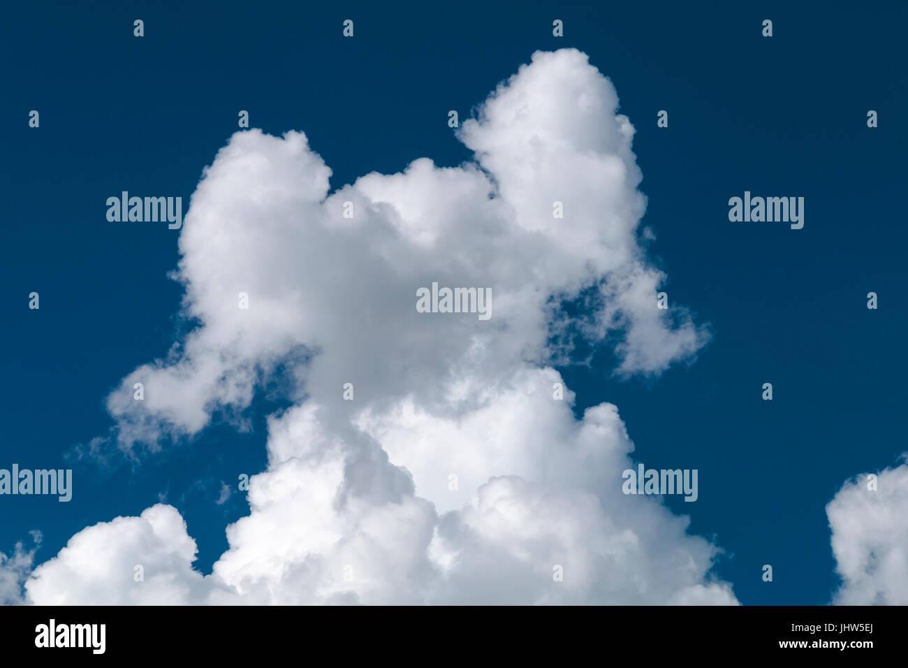 Una nuvola che sembra come una figura, modello o di persona con i bracci sollevati. Immagini Stock