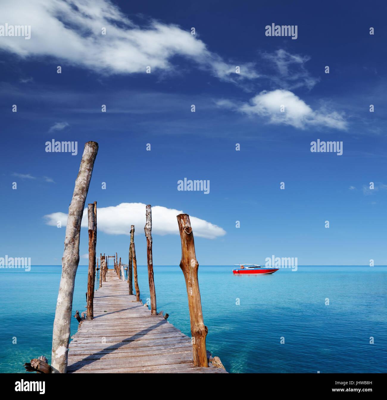 Il molo di legno su un isola tropicale, mare e cielo blu Immagini Stock