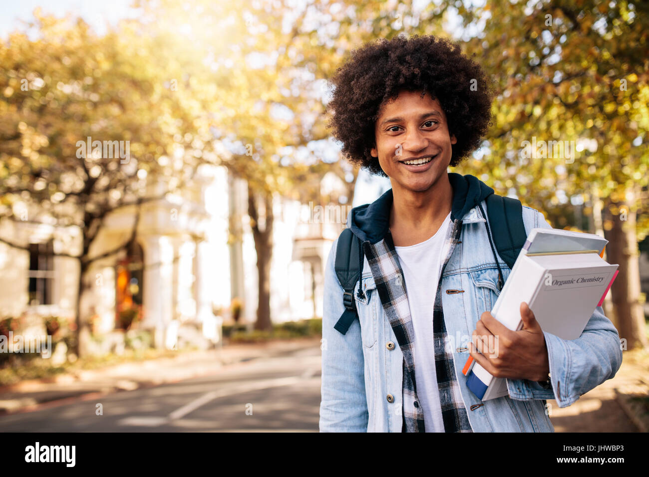 Giovani afro american studente di ritorno dal collegio. Maschio giovane studente universitario con libro in college Immagini Stock