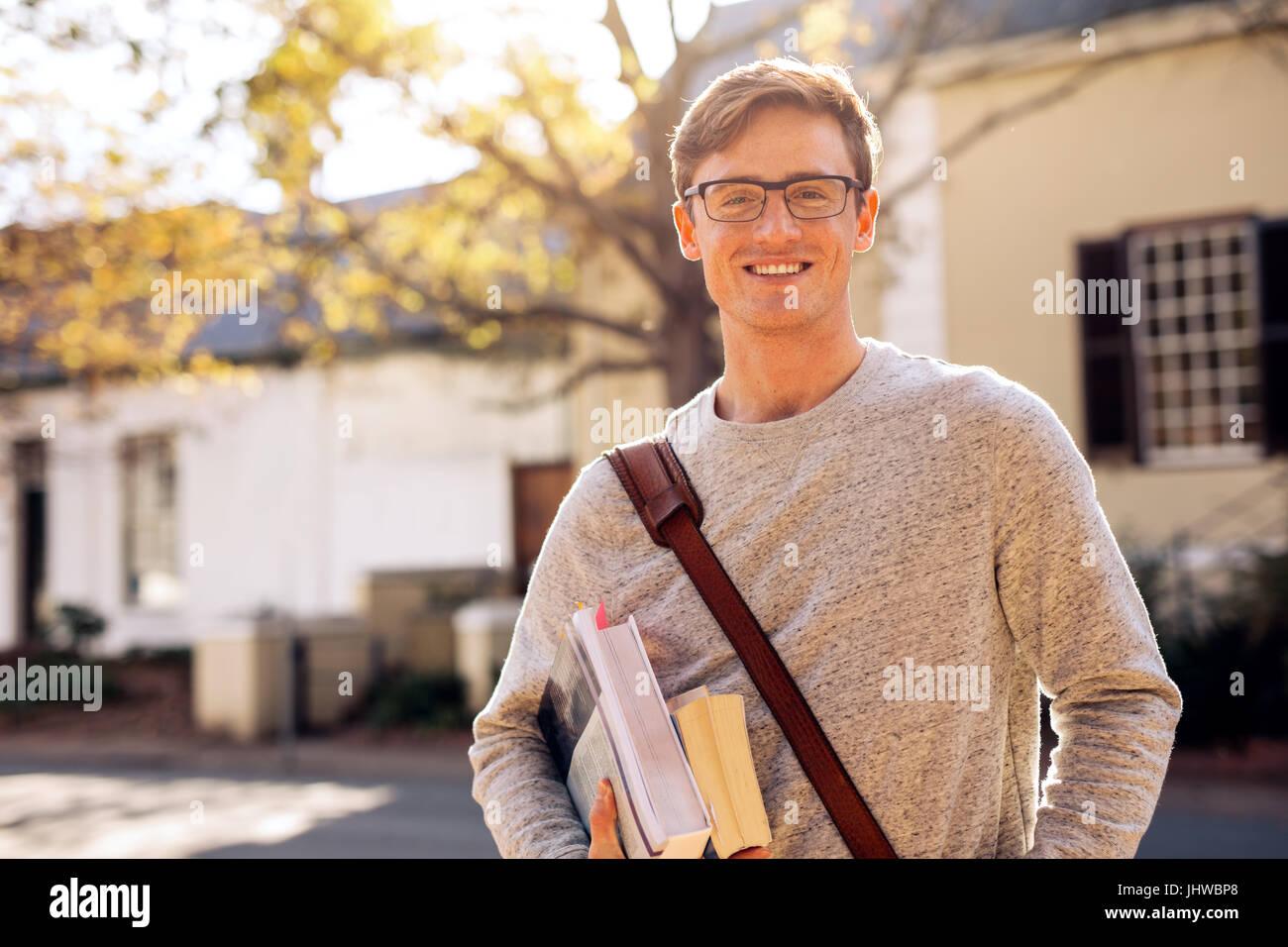 Felice collegio maschile studente all'aperto con i libri. Giovane studente universitario con libri in campus. Immagini Stock