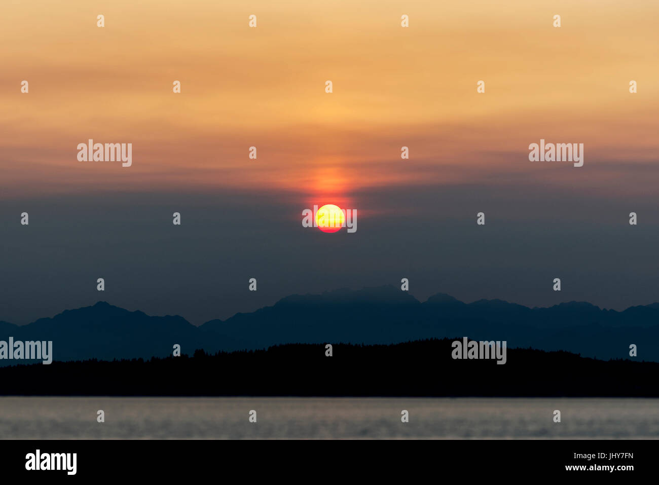 Sun centrato sulle montagne e sul mare al tramonto Immagini Stock