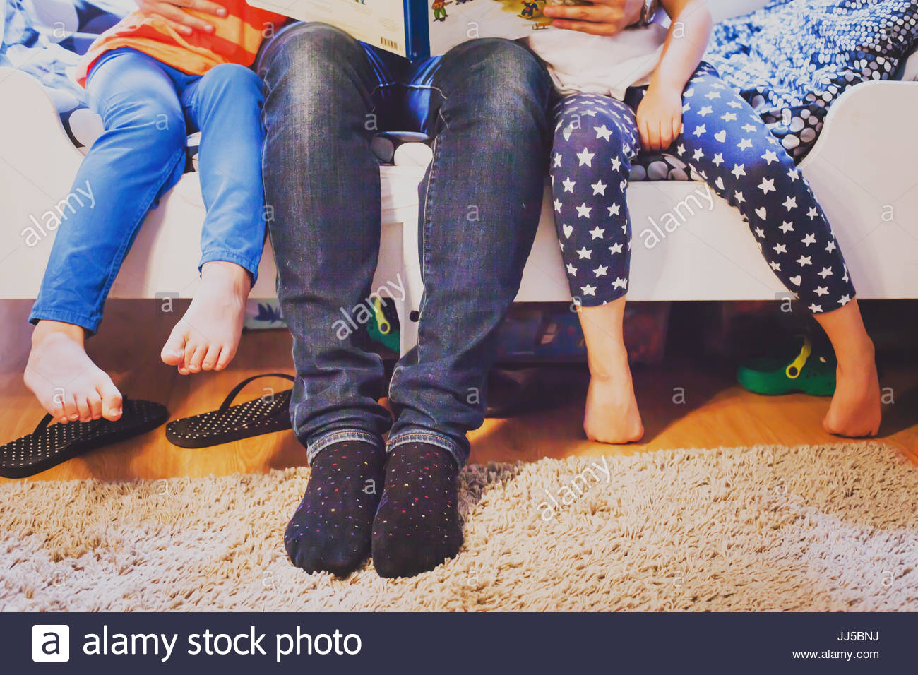 Padre a casa con due bambini seduti insieme e la lettura di libro, gambe di famiglia Immagini Stock
