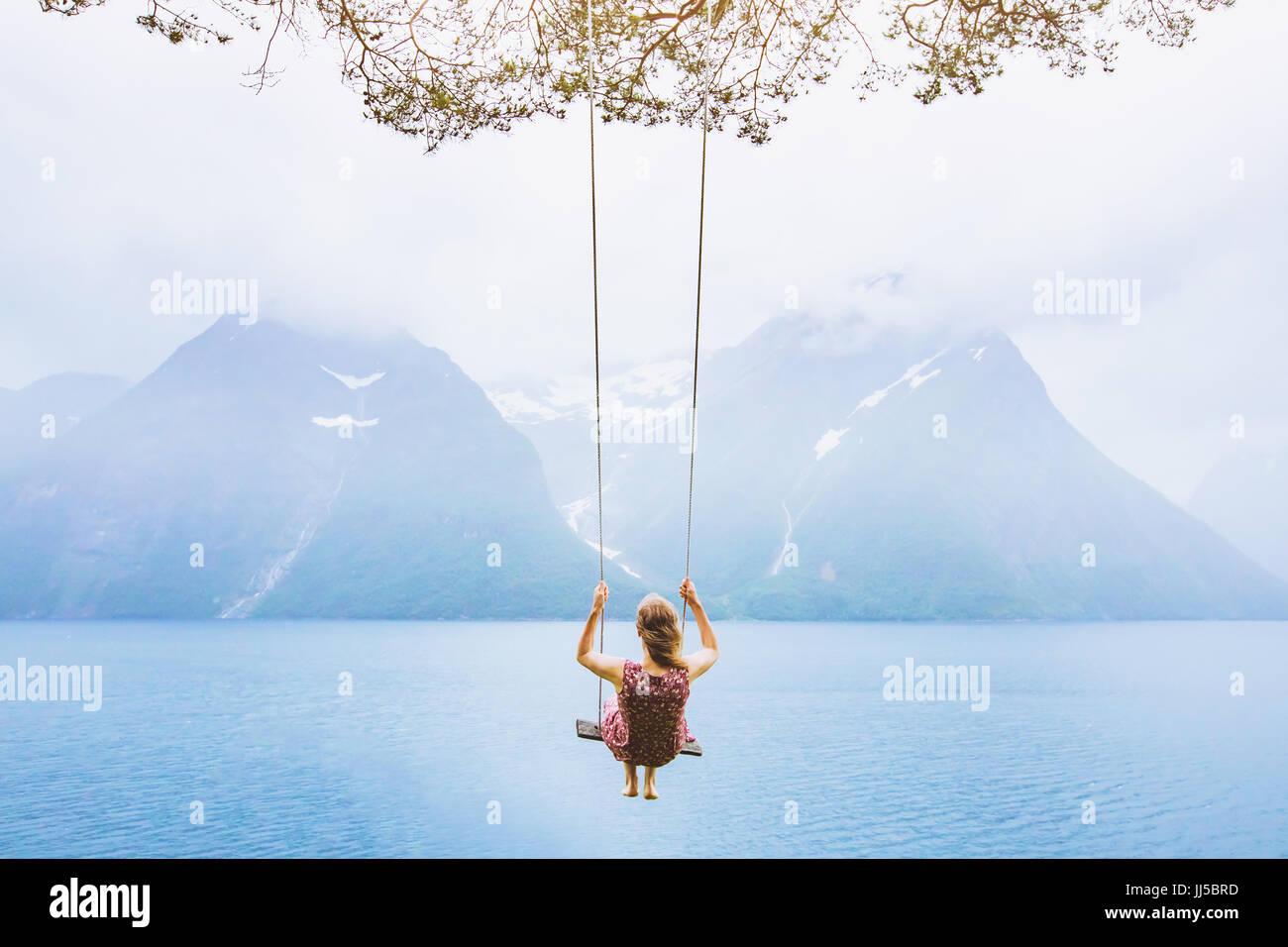 Concetto di sogno, bella giovane donna sull'altalena in Fjord Norway, suggestivo paesaggio Immagini Stock