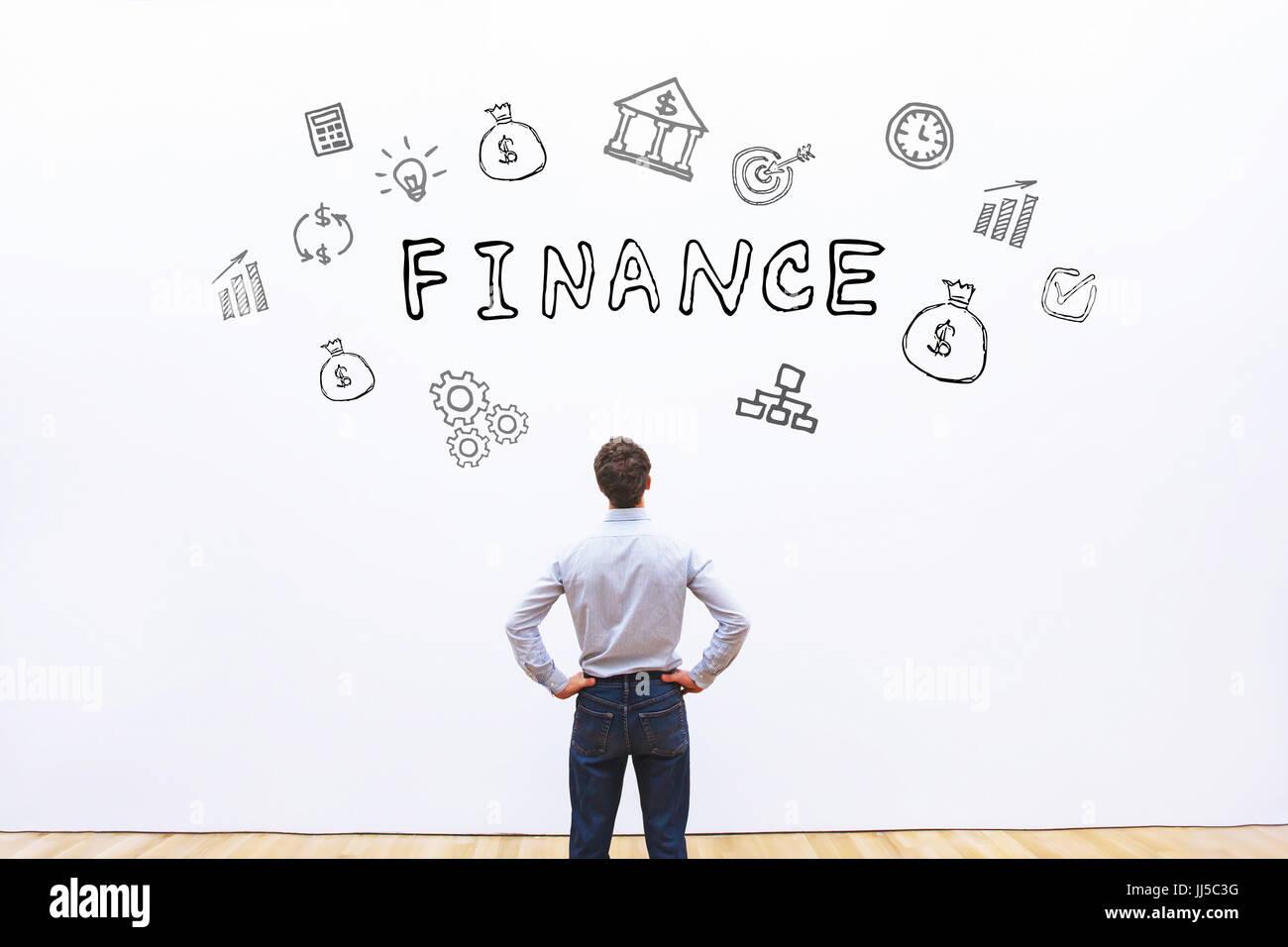 Concetto di finanza, uomo d affari guardando disegnate word su sfondo bianco Immagini Stock