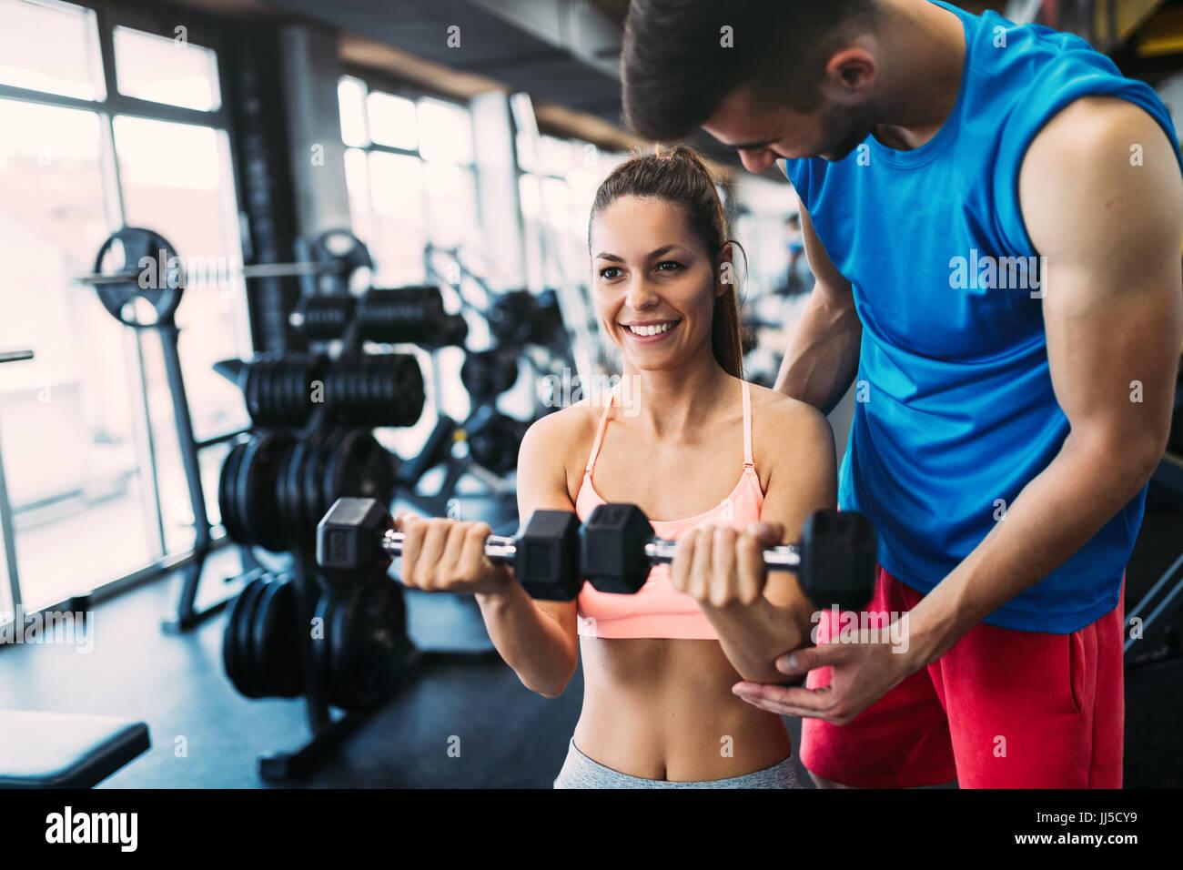 Bella donna facendo esercizi in palestra con personal trainer Foto Stock
