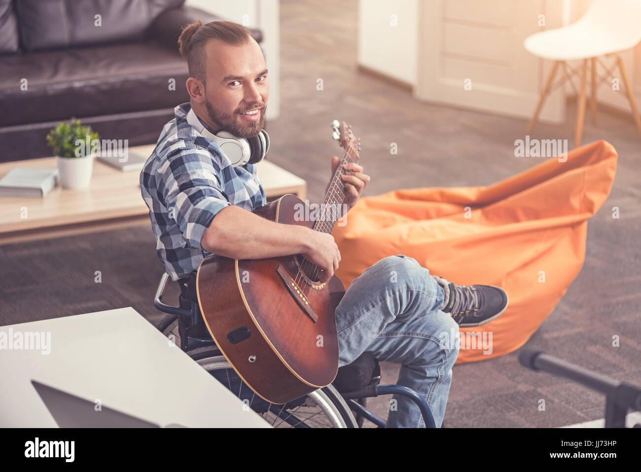 Felice giovane maschio in posa con uno strumento musicale Immagini Stock