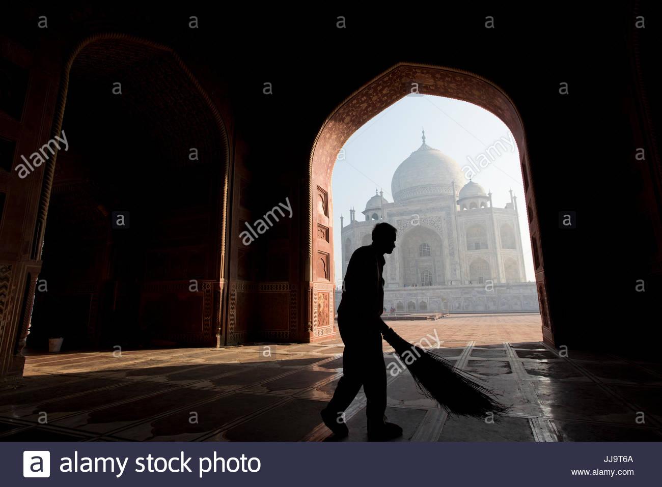 Un uomo indiano spazzare il modo di entrata della moschea accanto al Taj Mahal di Agra, India. Immagini Stock