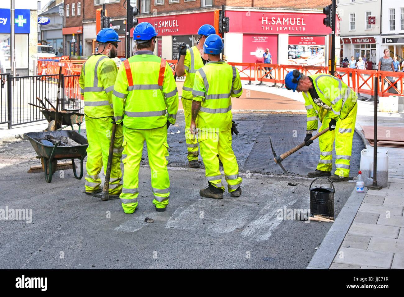 Un gruppo di operai resurfacing centro strada un uomo con piccozza altri quattro hanno tenuto una breve vacanza Immagini Stock