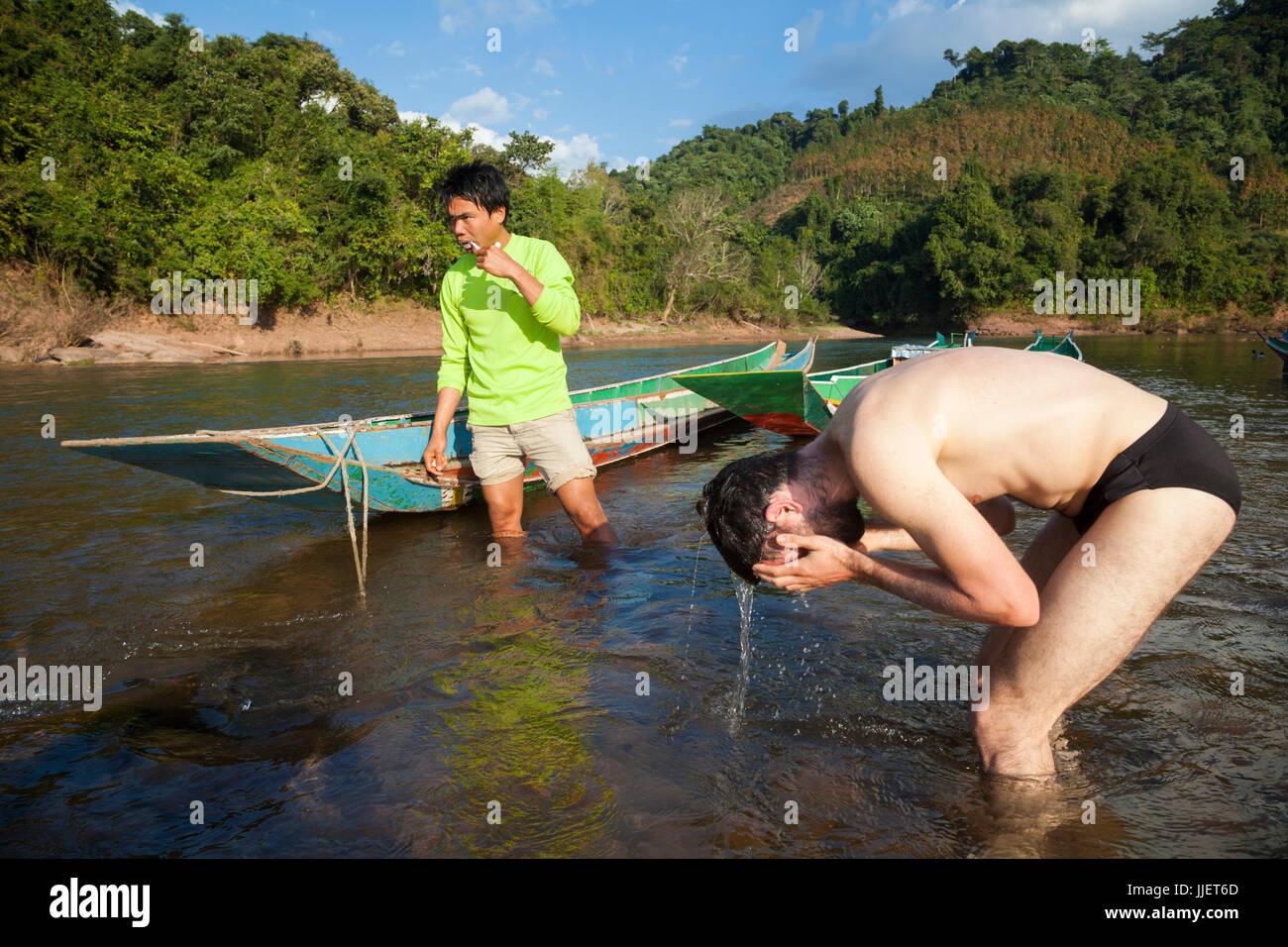 Mung (sinistra) e Robert Hahn spazzolare i denti e bagnarsi nel fiume Nam Ou fuori Muang Hat Hin, Laos. Immagini Stock