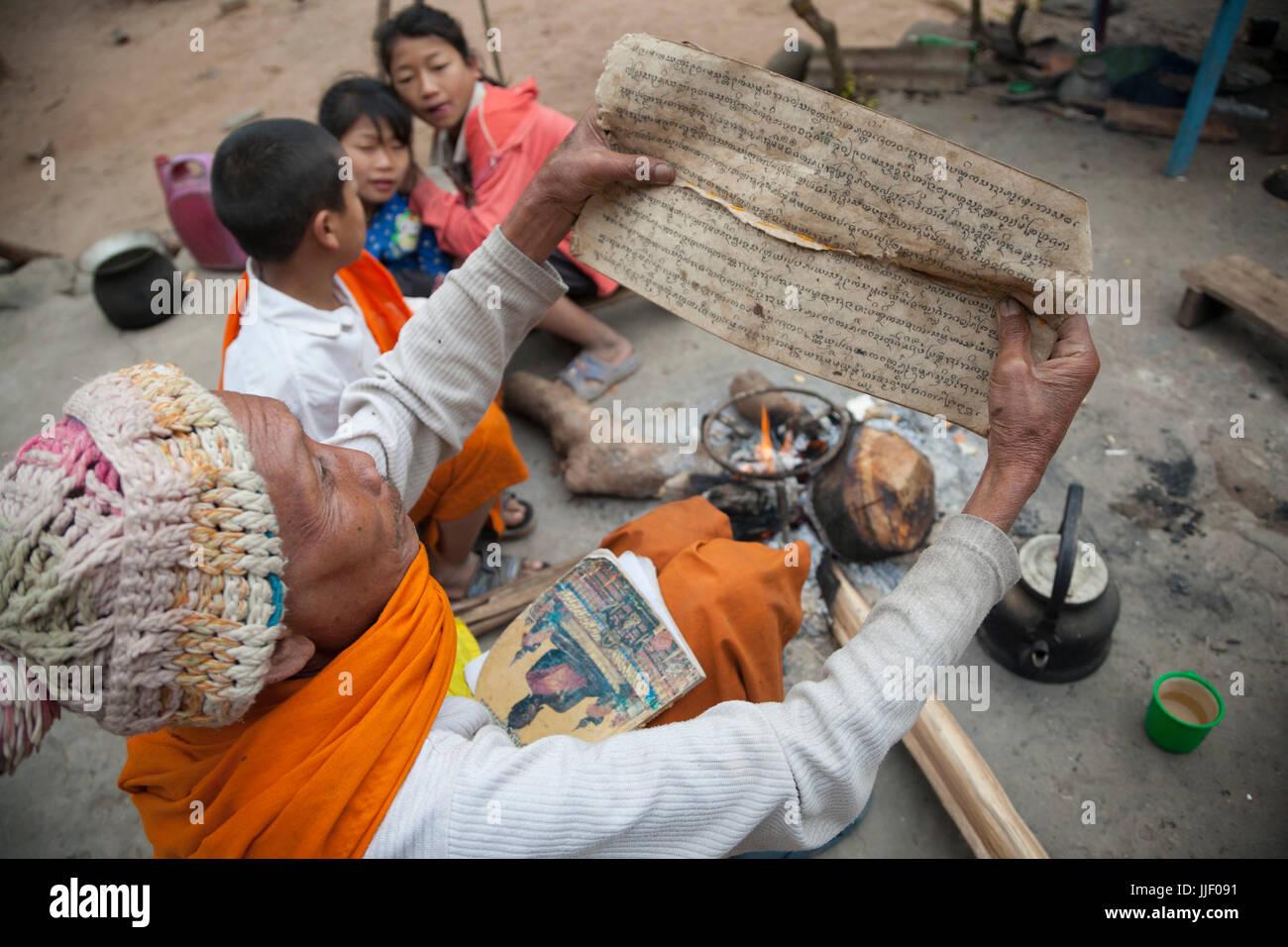 Il monaco residente detiene fino il sanscrito scrittura presso il monastero Buddista in Muang Houn, in Laos, in Immagini Stock