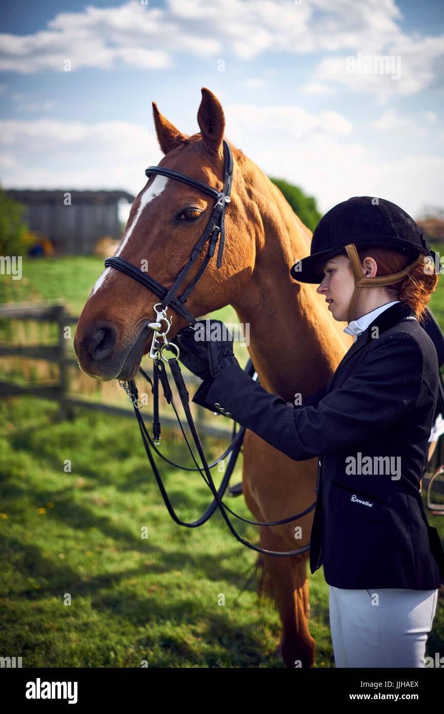 Una giovane donna di incollamento fino il suo cavallo prima di un giro. Immagini Stock