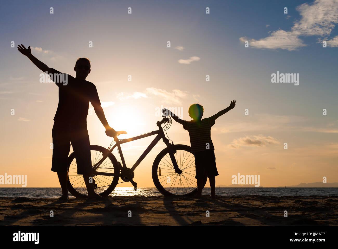Padre e figlio giocando sulla spiaggia al tramonto. Concetto di felice famiglia amichevole. Immagini Stock