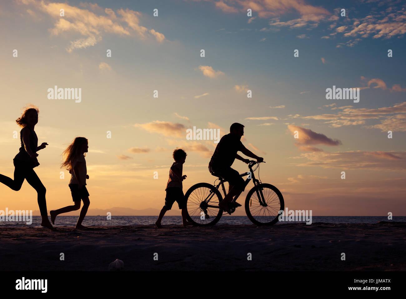 Padre e figli giocando sulla spiaggia al tramonto. Concetto di famiglia amichevole. Immagini Stock