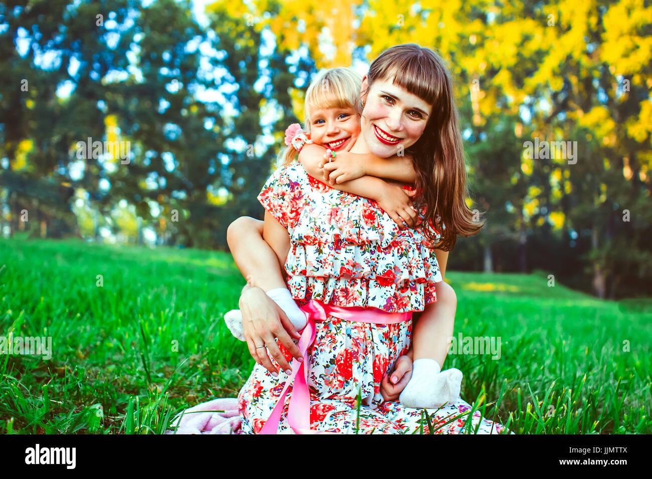 Carino giovane figlia su un piggy back ride con sua madre. guardando la fotocamera. Immagini Stock